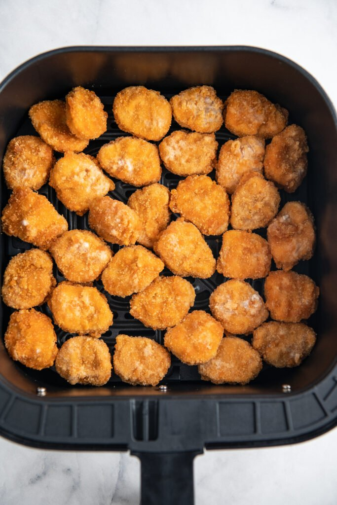 Overhead image of frozen chicken nuggets in an air fryer basket.