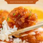 Orange chicken with rice on chopsticks.