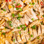 Up close image of Cajun Chicken Pasta with bell peppers and green onions sprinkled on top.