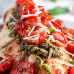 Side angle view of a chicken breast topped with melted cheese, pesto and roasted tomatoes.