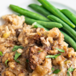 Up close image of a pork chop with stuffing on top on a white plate with green beans.
