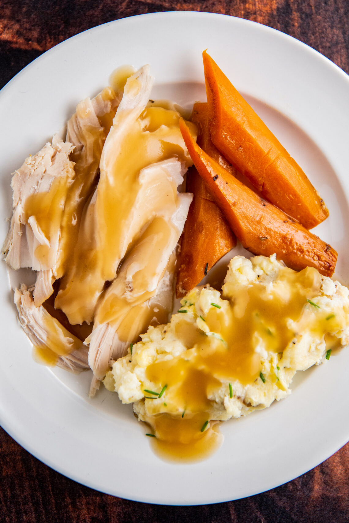 Up close image of turkey breast with gravy, mashed potatoes and carrots on a white plate.