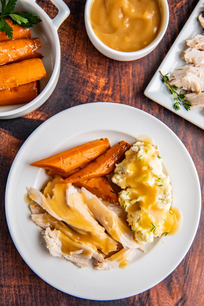 Overhead image of turkey breast sliced into pieces with gravy on top with carrots and mashed potatoes on a white plate.