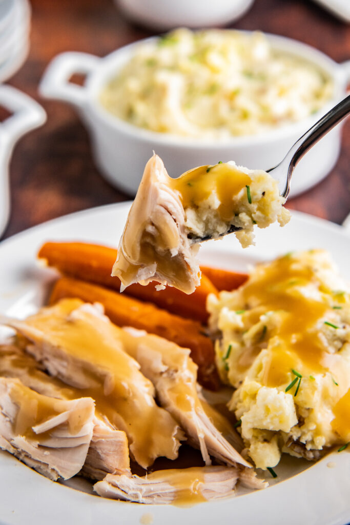A forkful of turkey and mashed potatoes with gravy on them.