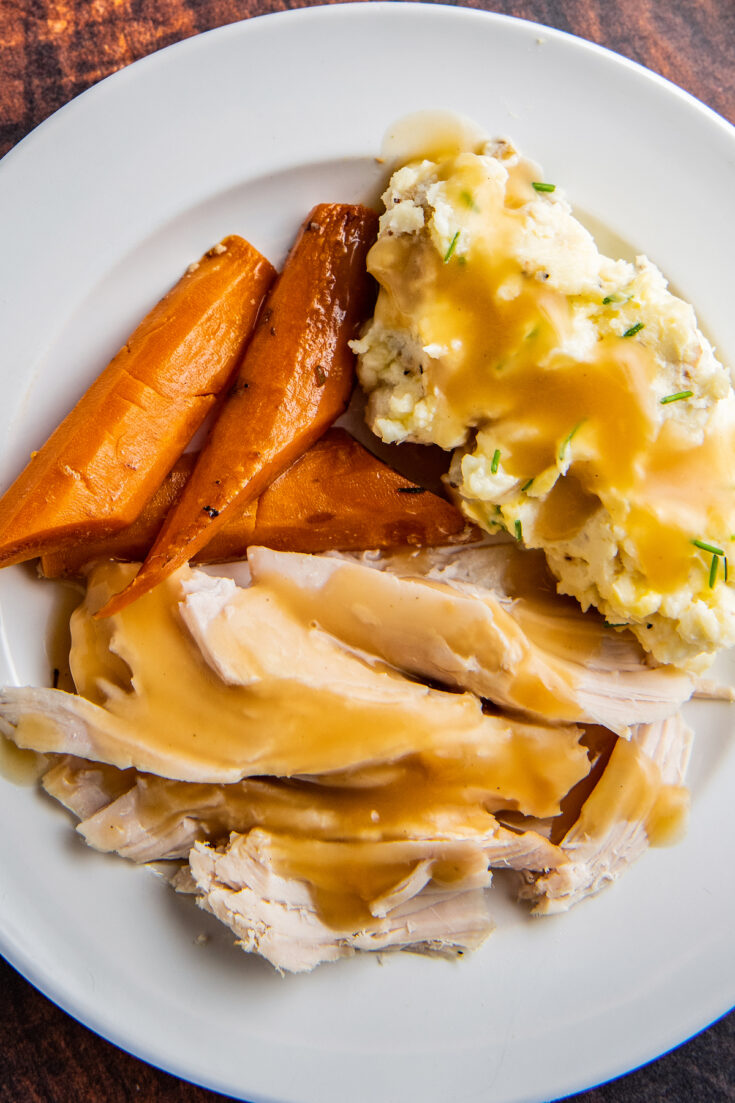 Overhead image of crockpot turkey breast sliced into pieces with gravy on top with carrots and mashed potatoes on a white plate.