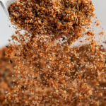 Seasonings being poured off a spoon into a bowl.