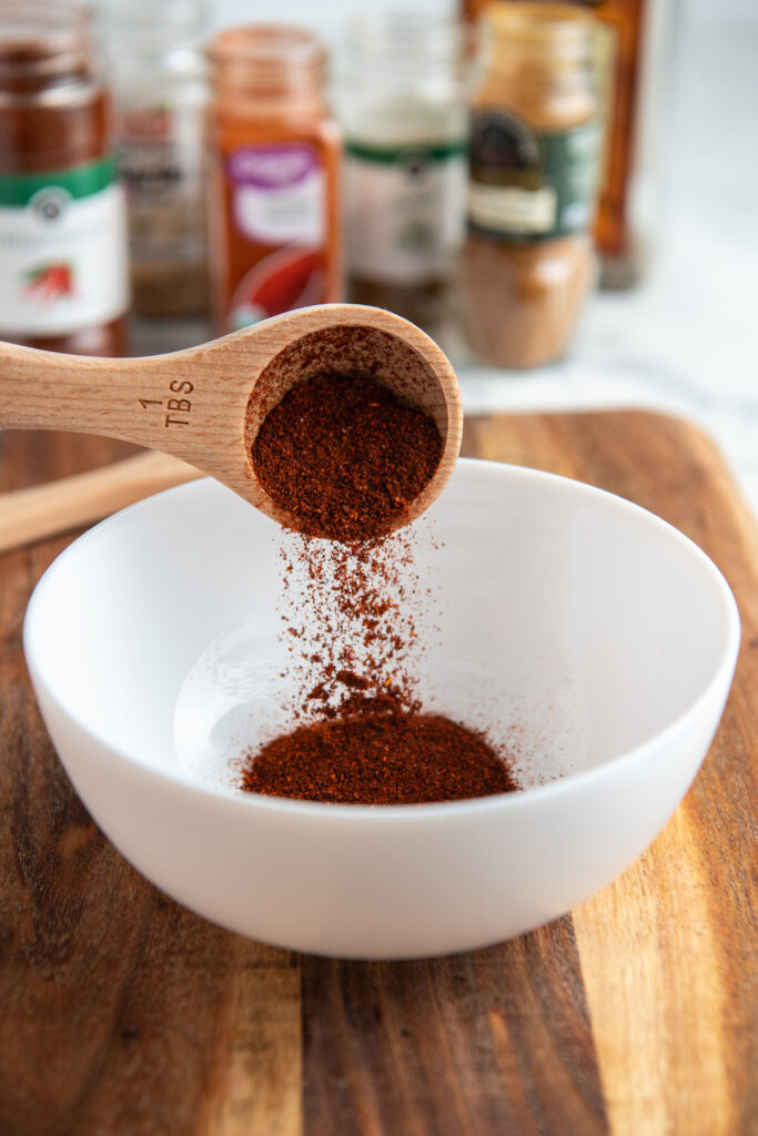 chili powder being poured into a white bowl with a wooden spoon.