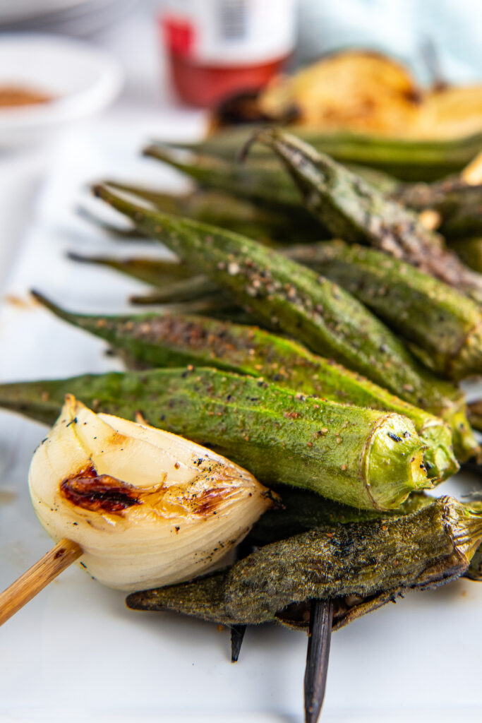 up close picture of okra and onion grilled on a skewer. the food is done and a little charred