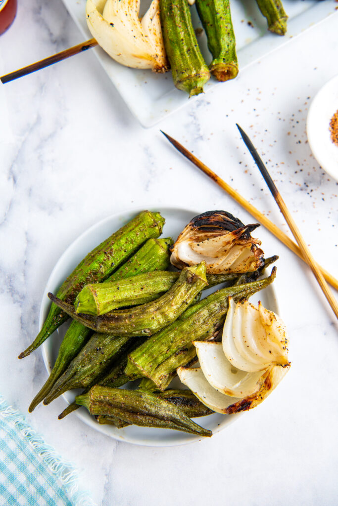 Grilled okra with seasonings on it on a white plate with onion.