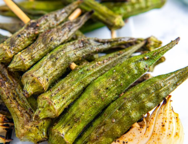 Grilled okra with seasonings on it on a skewer with onion.