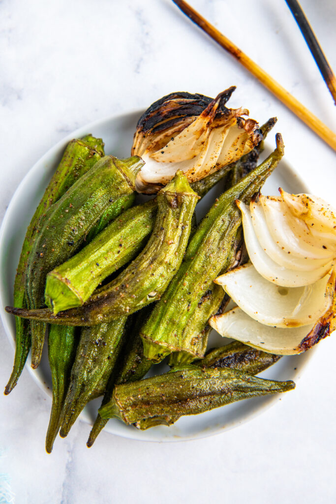grilled okra and onion on a plate off the skewer and ready to eat
