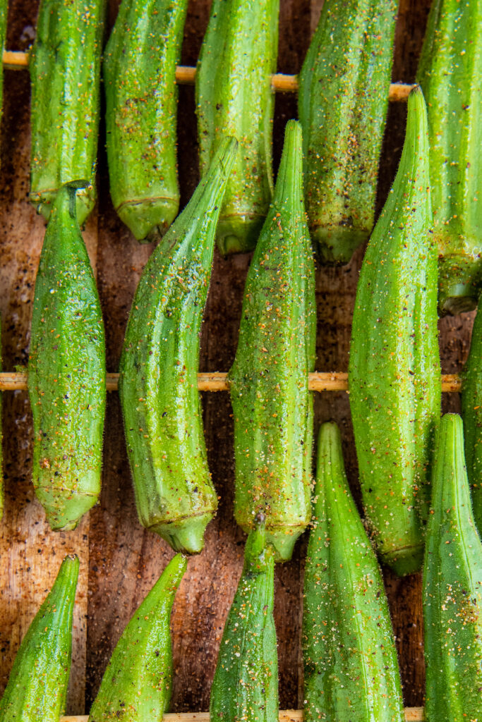 Up close image of okra on a skewer with seasoning on it.
