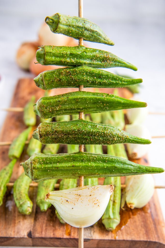 Okra on a skewer with an onion at the bottom.