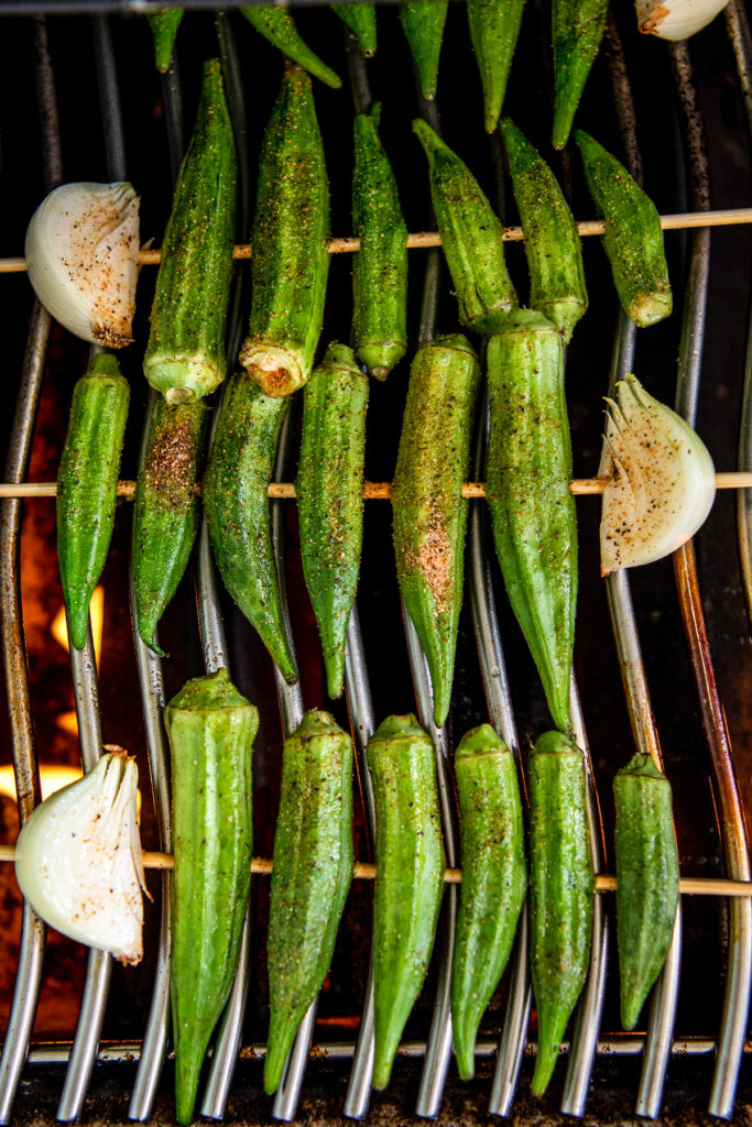 Okra on wooden skewers on a grill.