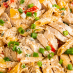 Overhead image of cajun chicken pasta in a pot with green onions on top.