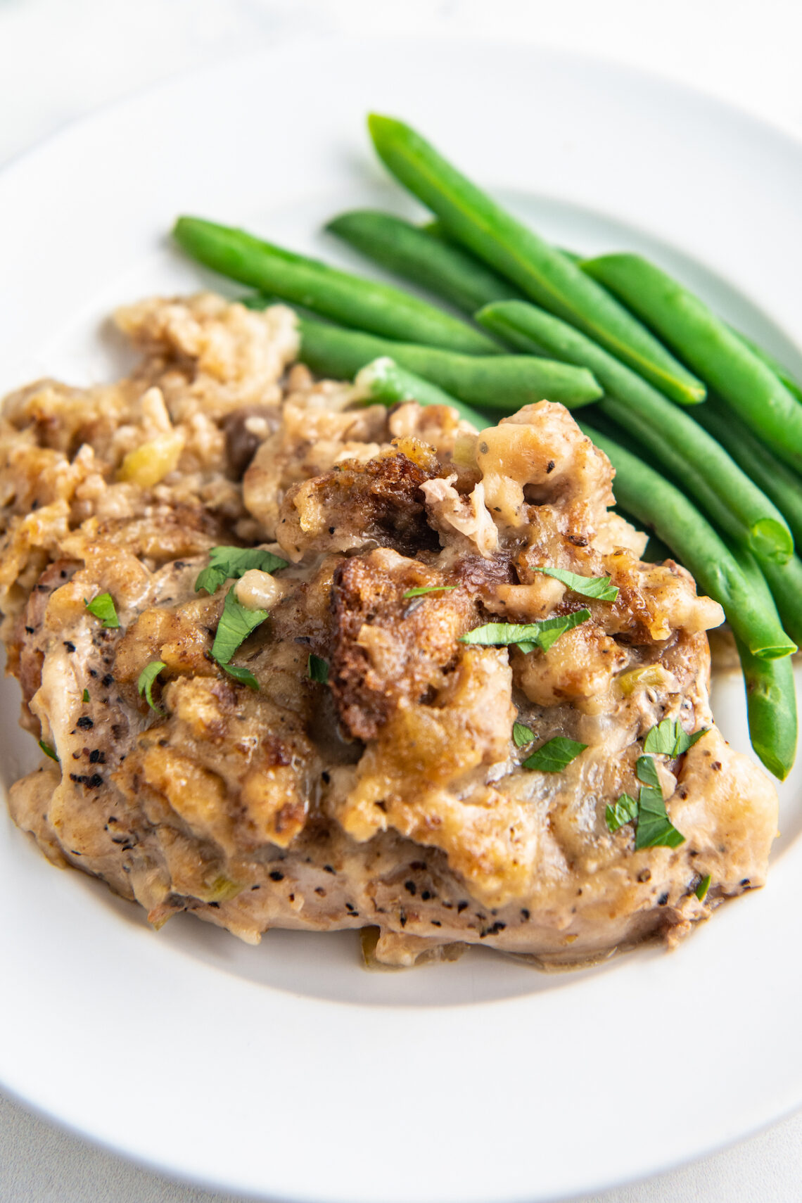 Up close image of slow cooker pork chops on a white plate with stuffing on top and green beans on the side.