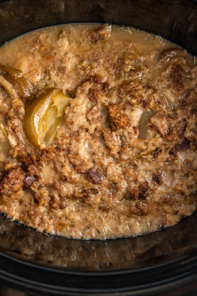 Overhead image of cooked stuffing on top of pork chops with gravy in a crockpot.