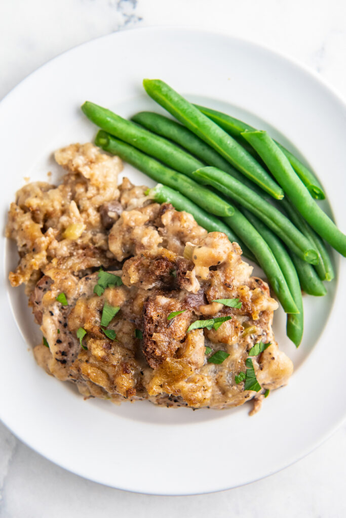 Overhead image of pork chop with stuffing on a white plate with green beans.