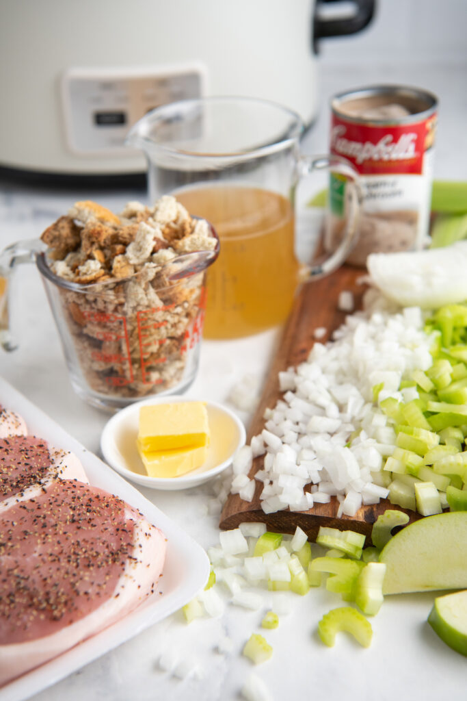ingredients you need to make porch chops and stuffing. pictured is onion, celery, pork chops, butter, Campbell's soup can and measuring tools