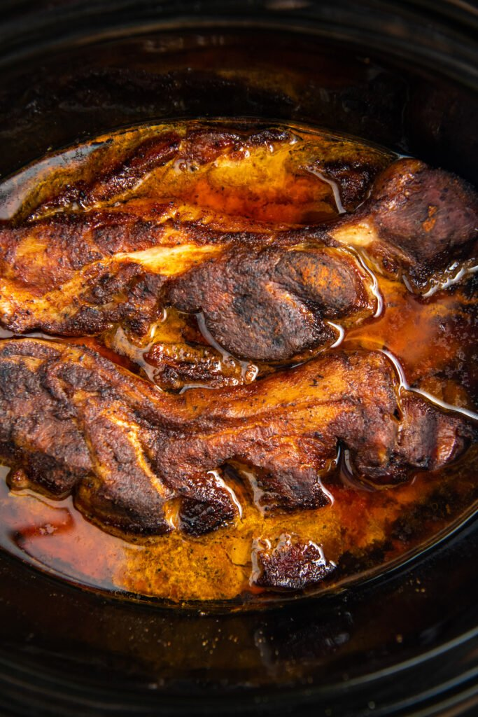 cooked ribs in black slow cooker