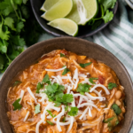A bowl of mexican white chicken chili with spoons and lime wedges with a crockpot in the background.