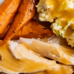 Overhead image of turkey breast with gravy on top and carrots and mashed potatoes on a white plate.
