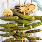 Grilled okra on wooden skewers with seasoning on top.