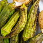 Grilled okra arrange don top of a white plate.