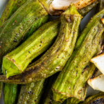 Grilled okra stacked on top of a white plate.