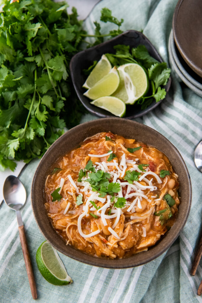 Mexican white chicken chili in a brown bowl with cheese and cilantro on top with lime wedges and a spoon.