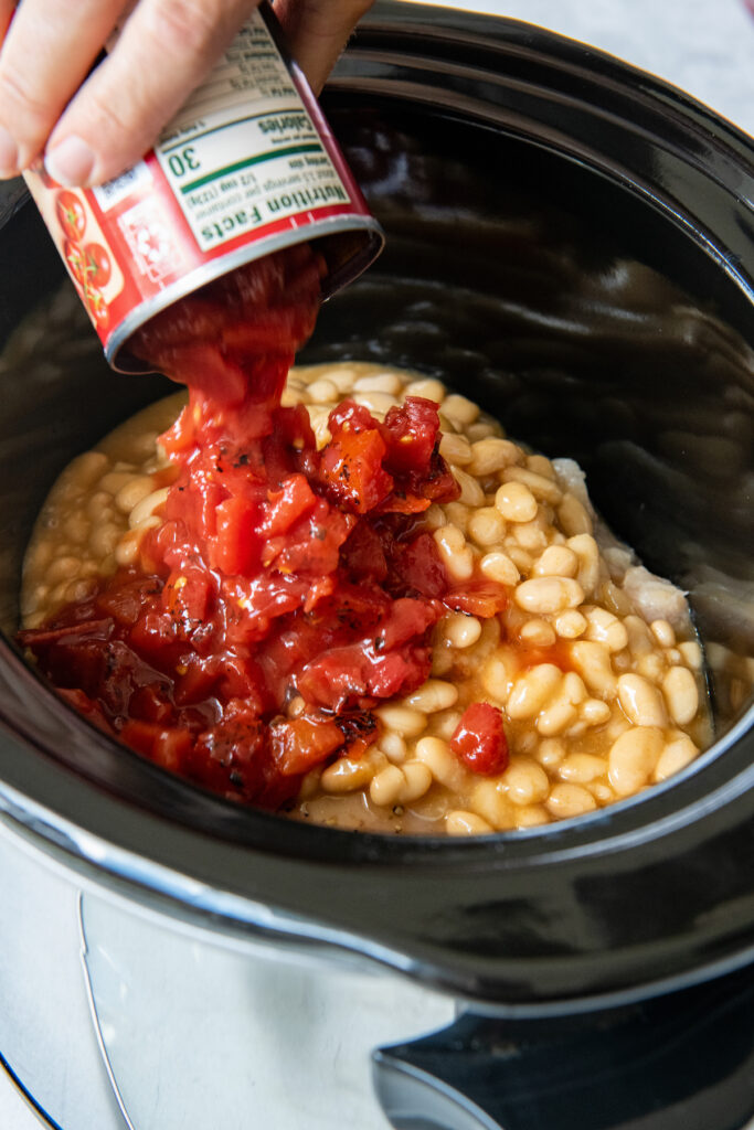 Fire roasted tomatoes being poured into the bowl of a crockpot.