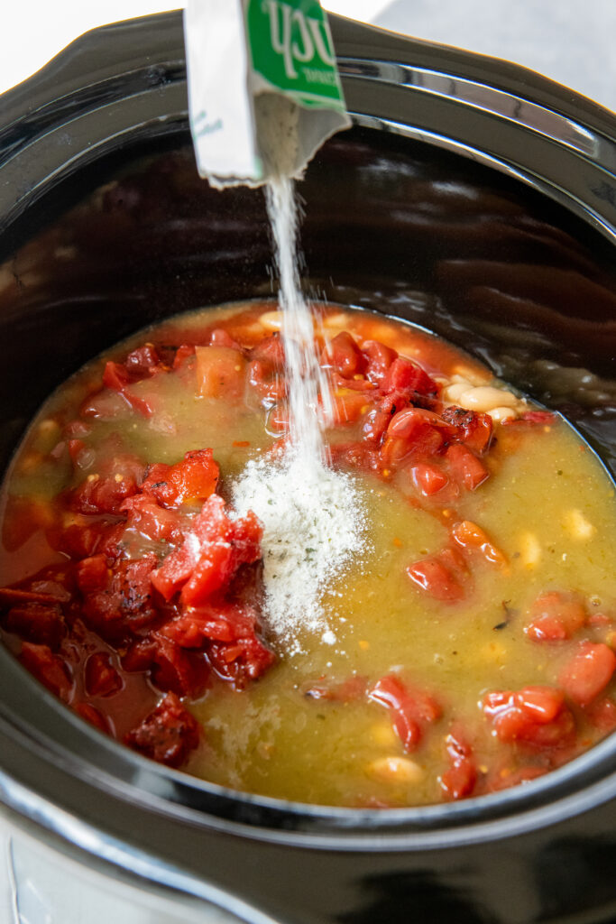 Ranch seasoning being poured into a crockpot with other ingredients in the crockpot.