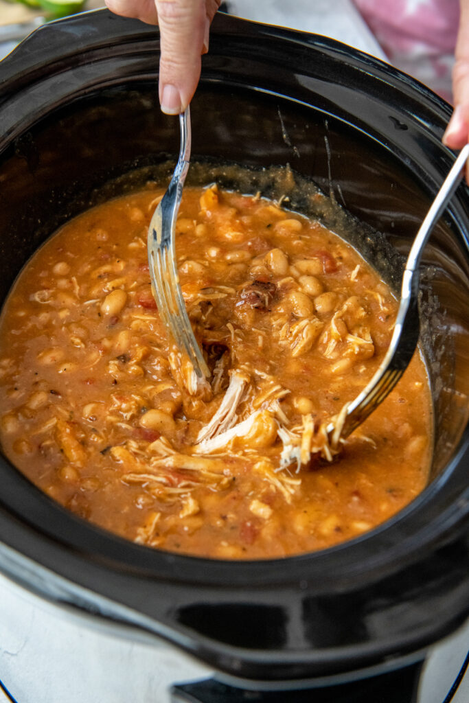 Two forks shredding chicken in a white chili in a crockpot.