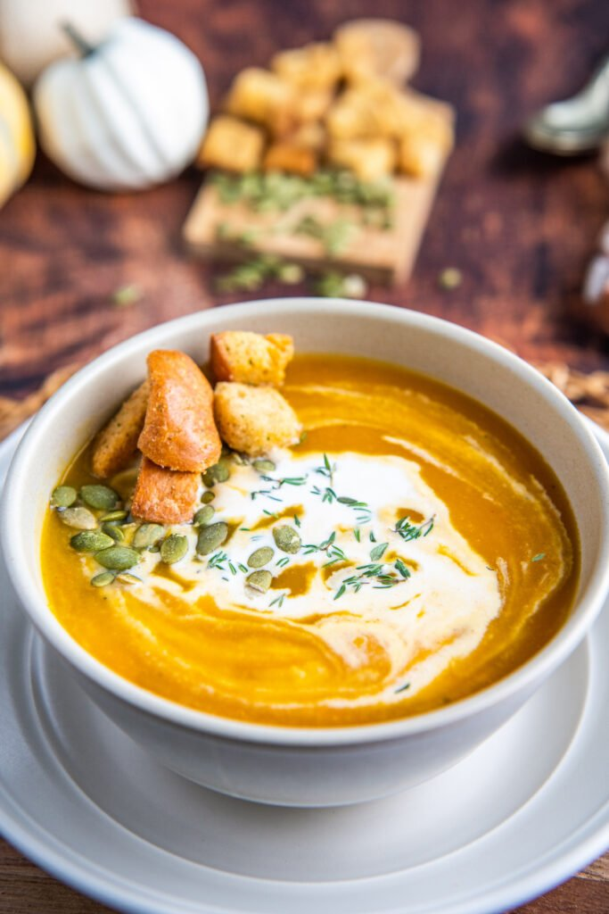 Butternut squash in a bowl with cream and pumpkin seeds on top.