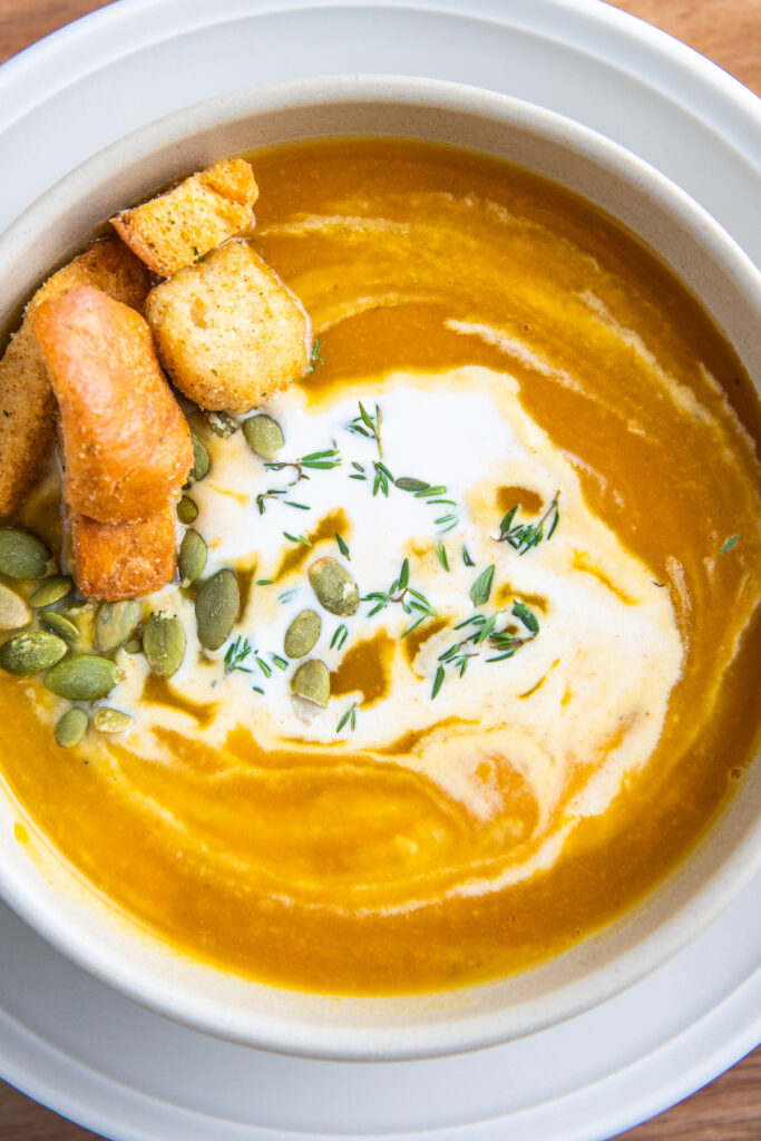 Up close image of a bowl of butternut squash soup with cream on top and croutons.