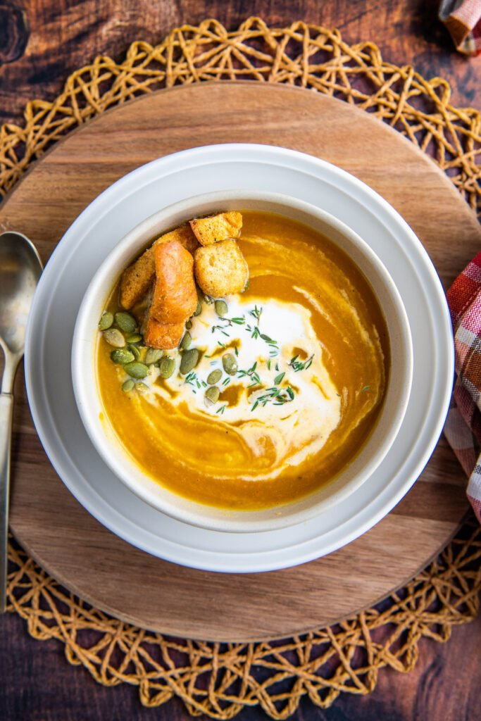 A bowl of butternut squash soup with cream, pumpkin seeds and croutons on top.