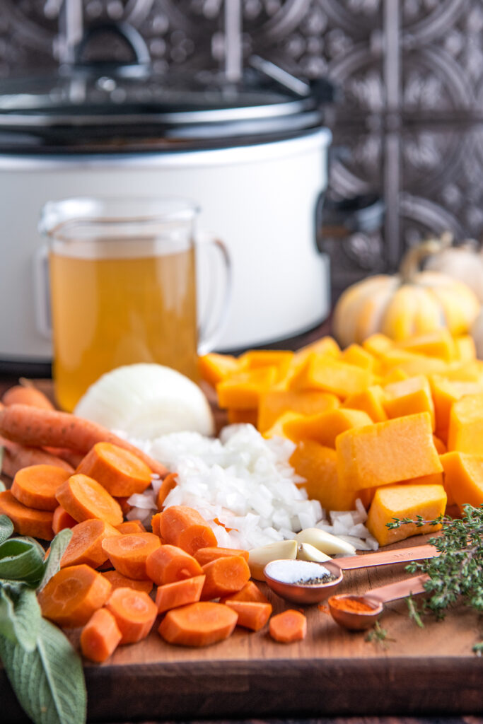 Ingredients for squash soup on a cutting board with a crockpot in the background.