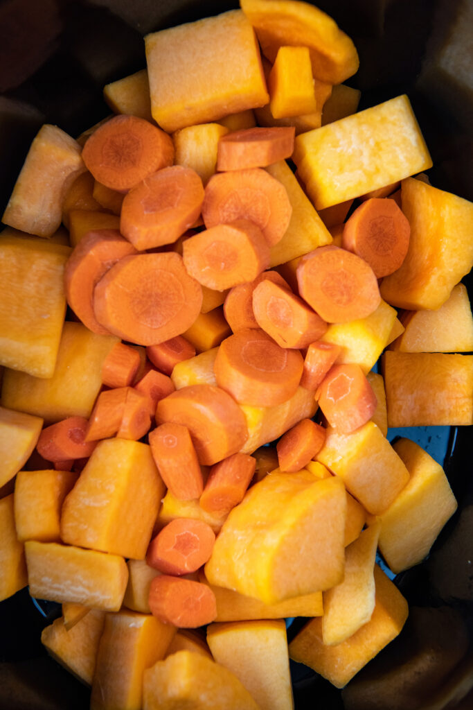 Butternut squash and carrots in the insert of a crockpot.