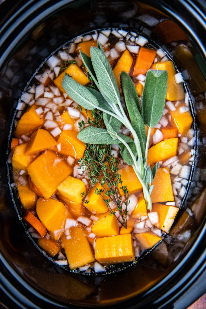 A crockpot filled with uncooked squash and herbs.