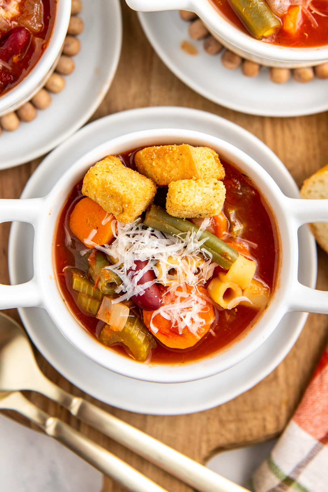 Up close image of minestrone soup in a white bowl with parmesan cheese and croutons on top.