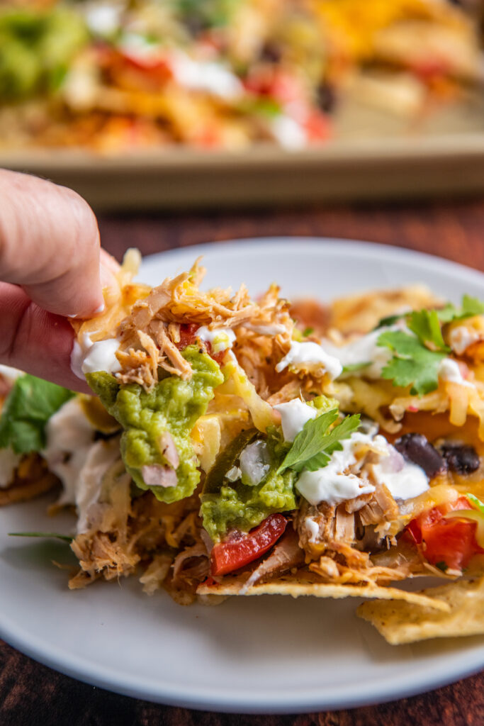 Pulled pork nachos on a white plate with fingers picking up a chip.