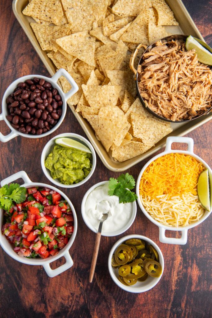 Ingredients for pulled pork nachos in white bowls.