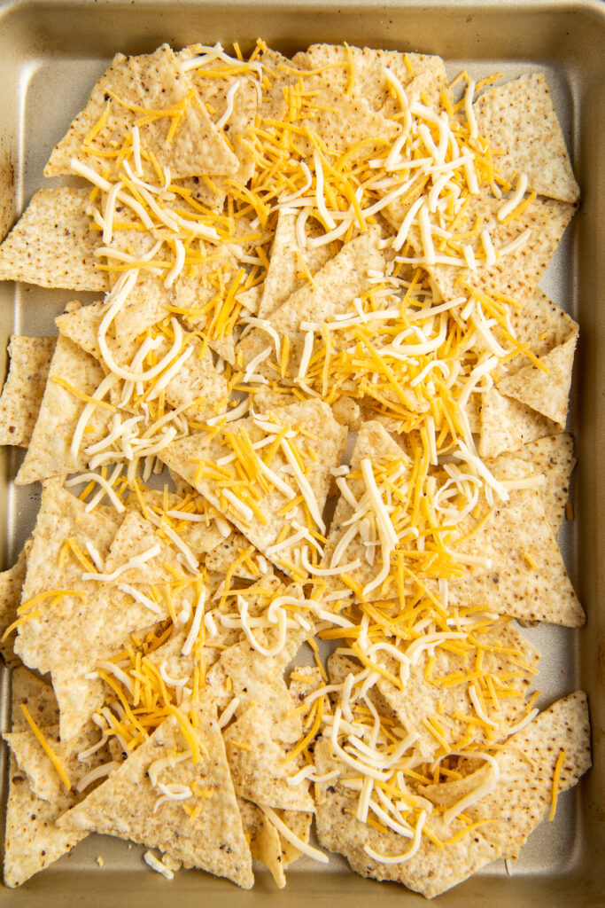 Tortilla chips on a sheet pan with cheese on top.
