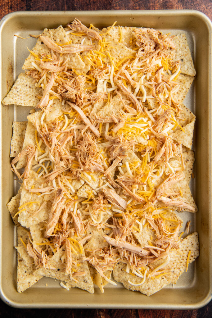 A baking pan is filled with tortilla chips with cheese and pulled pork layered on top.