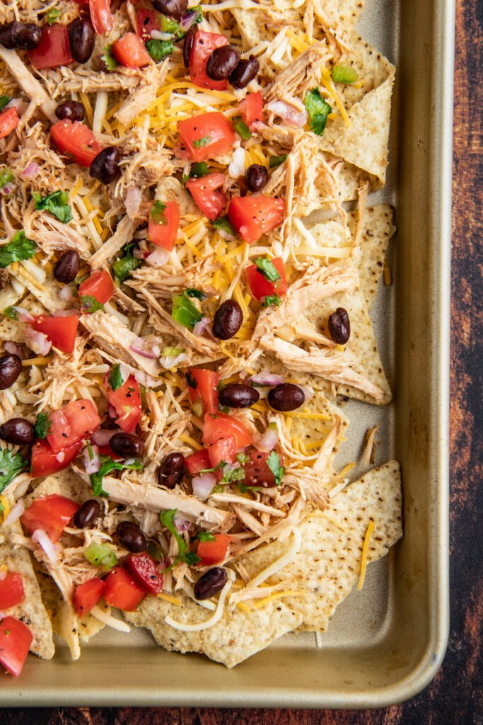 Tortilla chips topped with pulled pork, cheese and fresh pico on a sheet pan.