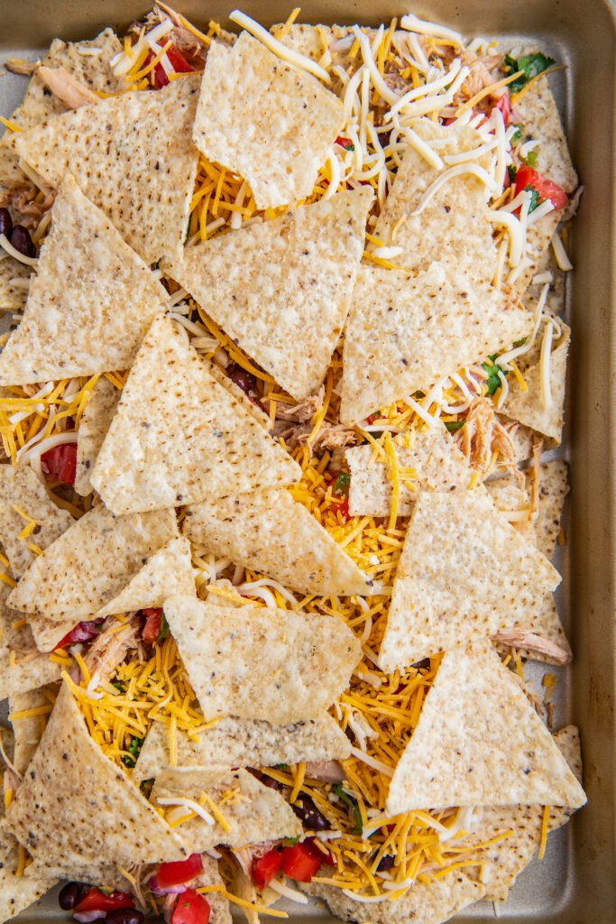 A layer of tortilla chips lined on top of nacho filling on a baking sheet.