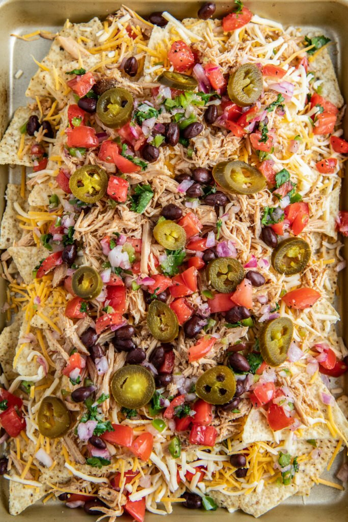 Nachos on a sheet pan with pickled jalapeños and fresh Pico De Gallo on top.