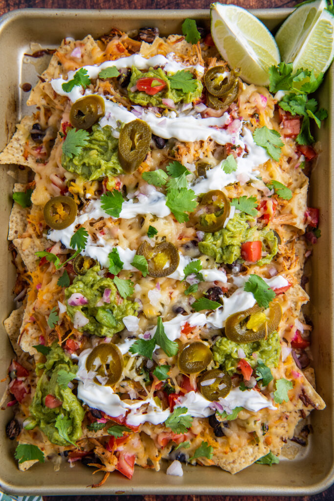 Overhead image of pulled pork nachos on a sheet pan with all the toppings piled on top.
