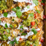 Pulled pork nachos on a sheet pan with all the toppings on top.